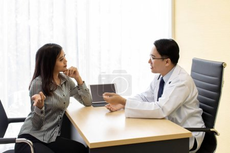 Photo for Doctor explaining treatment method to patient in beauty clinic using tablet - Royalty Free Image