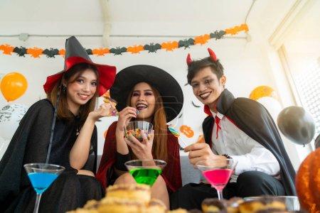 Photo pour Groupe de jeunes adultes et adolescents célébrant un festival de carnaval de fête d'Halloween en costumes d'Halloween avec nourriture et boisson sur la table . - image libre de droit