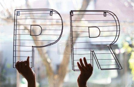 PR-Briefe vor dem Fenster. Zeiger halten 3D-Metallbuchstaben auf Hintergrundbeleuchtung. Marketing und Geschäftskonzeption.