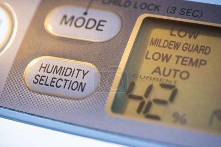 Photo pour Purificateur d'air et déshumidificateur. Concept pour chambre de déshumidification. Bouton de sélection de l'humidité. Affichage de pourcentage d'humidité. Dispositif de gros plan. - image libre de droit