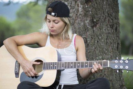 Photo pour Une jeune femme jouant de la guitare à l'extérieur - image libre de droit