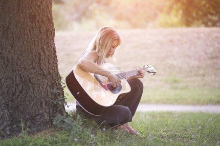 Photo pour Jeune femme jouant assis guitare contre un tronc d'arbre à l'extérieur - image libre de droit