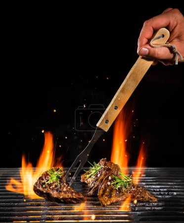 Delicious beef steaks on grill with Fire flames. Isolated on black background. Barbecue and grilling. Very high resolution image