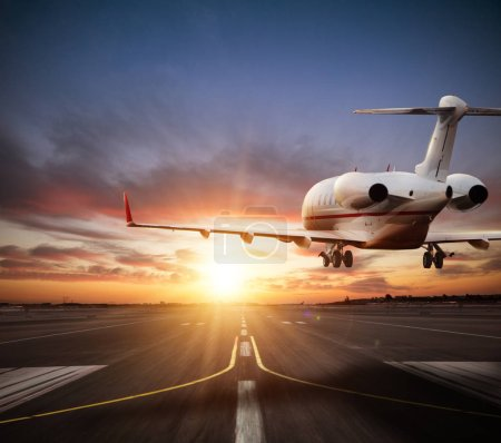 Private jet plane landing on runway in beautiful sunset light. Modern and fastest mode of transportation, business and succesfull style of life.