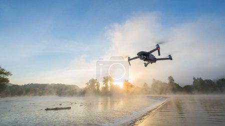 Drone copter with digital camera, blur river on background. Modern technology, UAV concept. Beautiful outdoor non urban scenery.