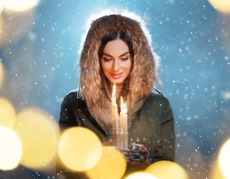 Photo for Cute brunette young woman holding candles. Concept of winter, Christmas and spirituality. - Royalty Free Image