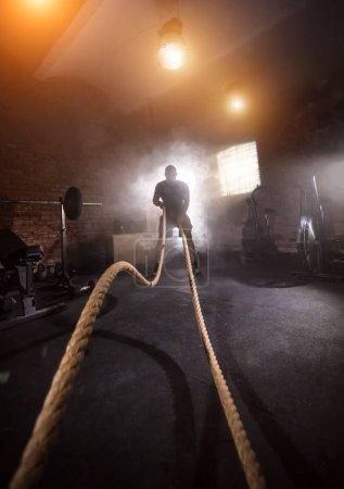 Photo pour Jeune homme faisant de l'exercice dur séance d'entraînement à l'intérieur de la salle de gym avec ondulation de corde. Humeur cinématographique avec poussière, éclairs dramatiques et fumée. Mode de vie actif et sain . - image libre de droit