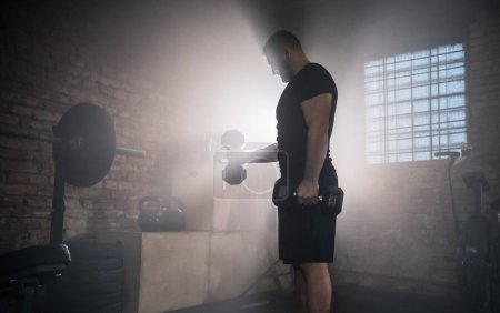 Photo for Weightlifter flipping one-handed dumbbell and preparing for workout in gym interior. Cinematic mood with dust, dramatic lightning and smoke. Active and healthy lifestyle. - Royalty Free Image