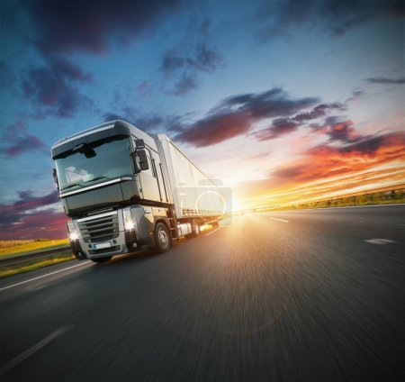 Photo for European truck vehicle on motorway with dramatic sunset light. Cargo transportation and supply theme. - Royalty Free Image