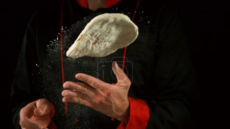 Photo for Freeze motion of cooker processing yeast pizza dough. Food preparation concept, ingredients around - Royalty Free Image