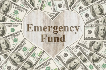 Photo for The love to have an emergency fund message, One hundred dollar bill in the shape of a heart with a weathered wood heart with text Emergency Fund - Royalty Free Image