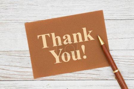 Photo pour Message de remerciement sur carte de vœux marron avec stylo sur un bois de blanchisserie altéré - image libre de droit