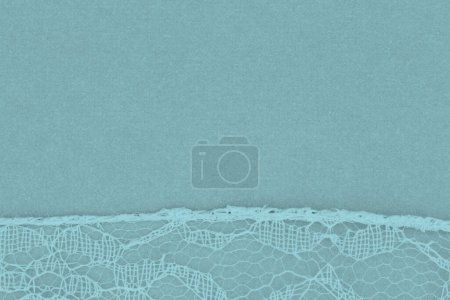 Photo for Delicate lace textured material on blue paper background with copy space for message or use as a texture - Royalty Free Image