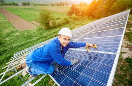 Construction worker connects photo voltaic panel to solar system using screwdriver. Professional installing and construction of solar system, smiling to the camera. Alternative energy concept