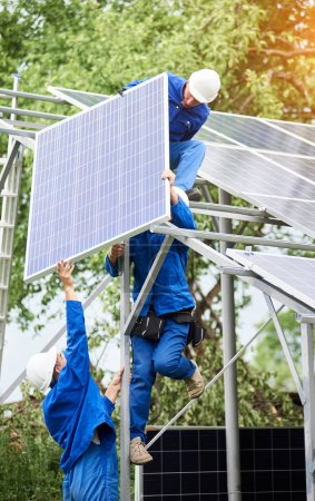 Installing of stand-alone solar photo voltaic panel system. Workers in hard-hats and blue overall lifting the solar module on metal platform. Alternative energy and professional construction concept.
