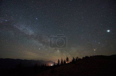 Fantastic mountains view at night. Steep hills covered with forest, fir-trees silhouettes against dark blue sky with bright sparkling stars and distant light on horizon. Beauty of nature concept.