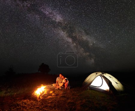 Happy tourist family camping in mountains by night. Husband and wife with small daughter sit on tree trunk in front of tent at burning campfire and look in camera. Tourism and traveling concept.