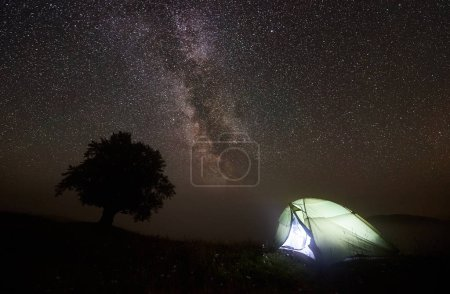 Fantastic night view of brightly lit from inside tourist tent camping in mountain valley and big tree against night sky with milliards of sparkling stars and Milky way. Tourism and traveling concept.