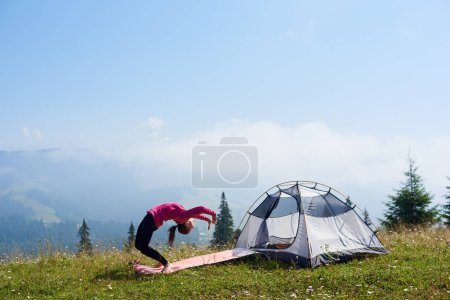 Young slim barefooted woman doing gymnastic exercises on green grass at small tourist tent under beautiful blue sky on bright sunny morning. Sport, tourism and mountain camping concept.