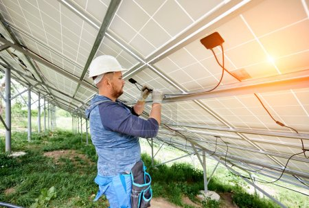 Photo for Installing and wiring of stand-alone solar photo voltaic panel system. Close-up of young electrician in hard-hat connecting electrical cables inside the solar modules. Alternative energy concept. - Royalty Free Image