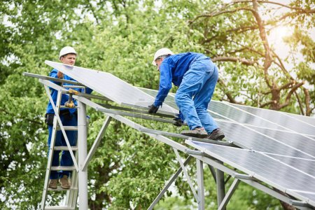 Installing of stand-alone solar photo voltaic panel system. Two workers assembling solar modules on metal platform on green tree background. Alternative energy and professional construction concept.