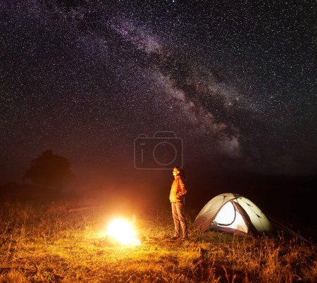 Camping in mountains. Young slim tourist woman standing near illuminated tents, watching brightly burning campfire under deep dark sky with lot of bright sparkling stars and Milky way on background