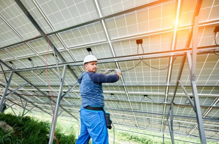 Young electrician in hard hat and rubber gloves wiring solar photo voltaic modules inside the new installed panel system on bright sunny day. Alternative energy and profitable investment concept.