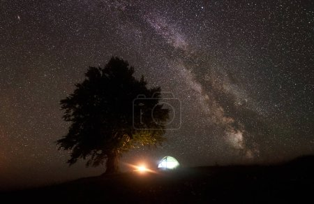Magical night view of illuminated tourist tent camping in mountain valley, bonfire and big tree against deep black sky with milliards of sparkling stars and Milky way. Tourism and traveling concept.