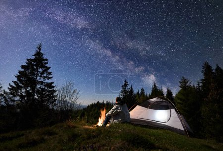 Man tourist sitting alone near illuminated tent at burning campfire on grassy valley, enjoying night blue starry sky with Milky way, pine trees forest on background. Beauty of nature, tourism concept
