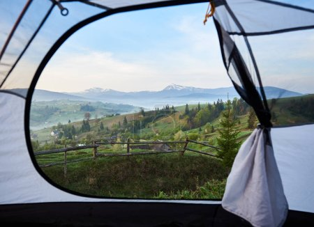 View of foggy valley, wooden pasture fence, shepherd huts, pine trees and distant mountains with snowy peak from inside of tourist tent. Tourism, camping, active lifestyle and recreation concept.