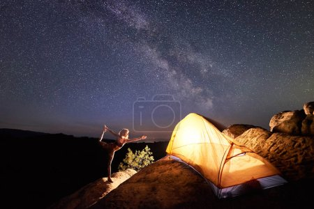 Slim woman in complicated posture standing on one leg on steep rock in front of tourist tent under starry night sky full of stars and Milky way. Yoga, active lifestyle, camping concept. Narajasana