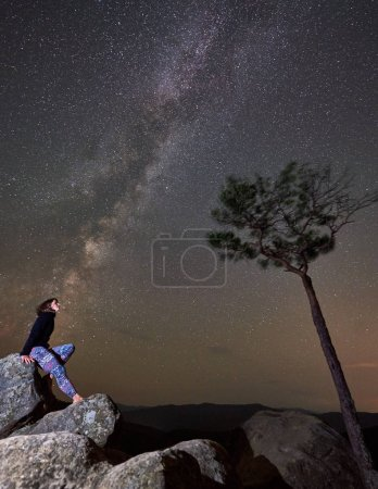 Young slim tourist woman sitting alone on top of huge boulder near tree under night starry summer sky with Milky way, enjoying mountain quietness. Tourism, hiking and active lifestyle concept
