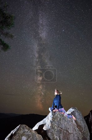 Young slim tourist woman sitting alone on top of huge boulder under night starry summer sky enjoying mountain quietness. Tourism, traveling, hiking, recreation and active lifestyle concept.