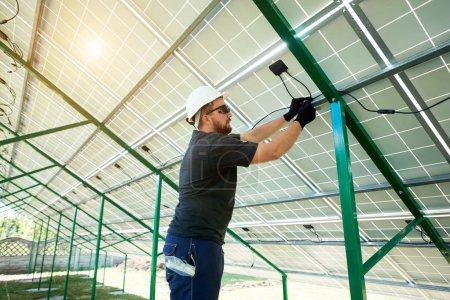 Foto de Trabajador profesional instalación de paneles solares en la construcción de metal verde, usando diferentes equipos, usar casco. - Imagen libre de derechos
