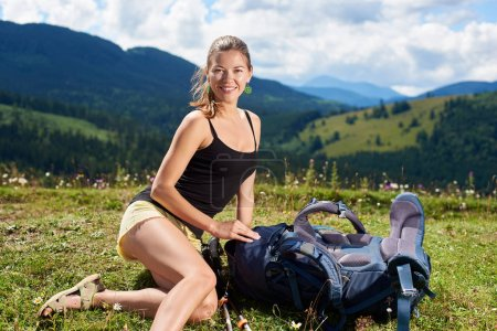 Attractive happy woman hiker hiking mountain trail, resting on grassy hill with trekking sticks and backpack, enjoying summer day in the Carpathian mountains. Outdoor activity, tourism concept
