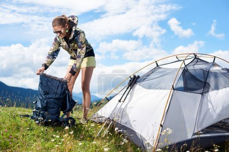Photo pour Touristique de la jeune femme randonnée montagne, debout près de tente, trucs d'emballage dans le sac à dos, appréciant le matin ensoleillé d'été dans les montagnes. Camping lifestyle concept aventure vacances plein air - image libre de droit