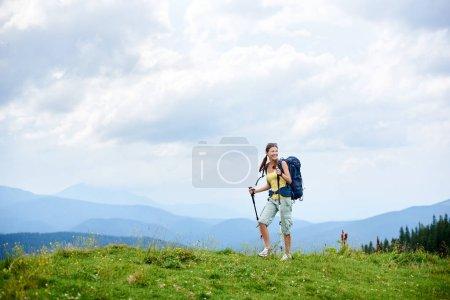 Foto de Deportivo sonriente mujer para mochileros senderismo en ruta de montaña de los Cárpatos, caminando por la colina cubierta de hierba, con mochila, utilizando senderismo palos, disfrutando el día nublado de verano. Actividad al aire libre, concepto de estilo de vida - Imagen libre de derechos