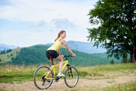 Photo for Athlete happy woman cyclist cycling on yellow mountain bike, enjoying summer day in the mountains. Outdoor sport activity, lifestyle concept - Royalty Free Image