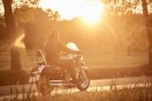"""Постер, картина, фотообои """"Вид сбоку бородатый мотоциклист, езда мотоцикл современные мощные крейсер вдоль пустых узкой проселочной дороге на закате на красивой золотой осенний пейзаж фона."""""""