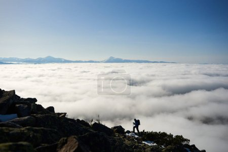 Photo for Silhouette of tourist hiker with backpack and trekking poles climbing steep rocky mountain slope - Royalty Free Image