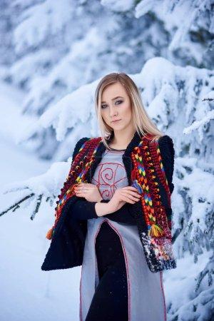 Photo pour Jolie femme en manteau de fourrure sans manches court brodé et décoré en peau de mouton dans la forêt d'hiver - image libre de droit