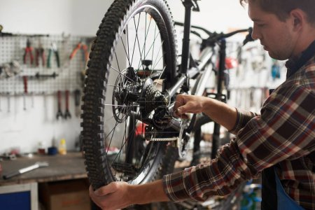 Photo for Male mechanic working in bicycle repair shop, repairman fixing bike using special tool, wearing protective work wear - Royalty Free Image
