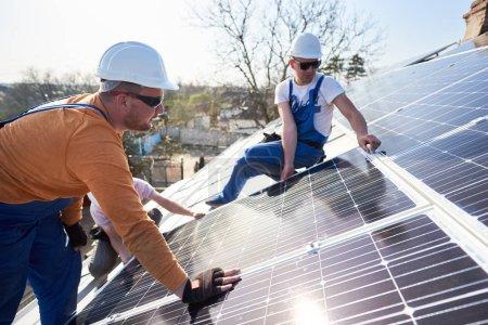 Foto de Electricistas módulo solar azul de montaje en techo de casa moderna. Concepto ecológico de energía renovable alternativa. - Imagen libre de derechos