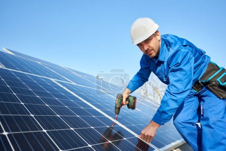 Photo for Male worker in blue suit and protective helmet installing solar photovoltaic panel system using screwdriver - Royalty Free Image