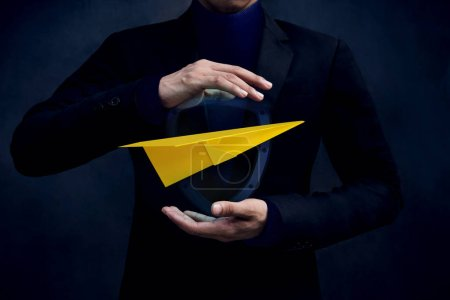 Travel Insurance Concept. Airlines industry Safe and Supporting Customer, Paper Airplane floating and Protected by Careful Gesture Hands of Businessman