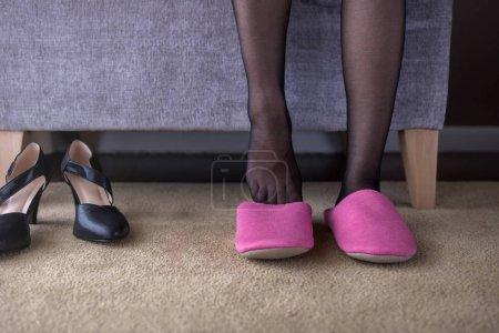 Photo pour Concept de soins de santé ou d'équilibre de vie. Femme d'affaires assis sur chaise dans la maison pour changer de chaussures de travail haut talon à chausson confortable. Vue de face - image libre de droit