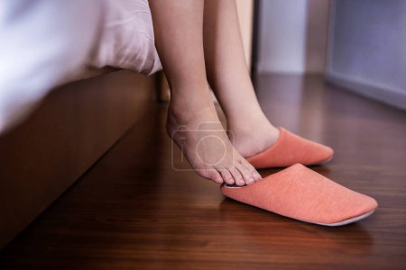 Relaxation and Comfortable Concept. person Waking up in the Morning and putting on Slipper Shoes in Bedroom