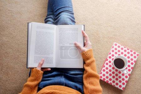 Foto de Concepto de lectura. Enfoque suave de mujer joven relajante por libro y café en acogedora casa, vista superior - Imagen libre de derechos