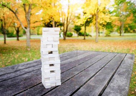 Photo pour Tour de bloc en bois jeu de pile sur la table dans le parc ou arrière-cour, Activités pour la famille et les amis à jouer en automne et automne saison - image libre de droit