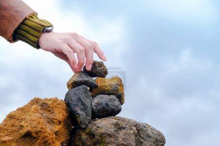 Photo pour Foi et Concept spirituel. Femme qui tente à une chute de la pierre naturelle sur le dessus de la pile. Montagne en arrière-plan - image libre de droit